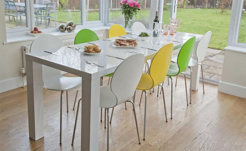 Ảnh cận cảnh mẫu bàn ăn hình chữ nhật màu trắng kết hợp ghế ngồi màu vàng, xanh lá
