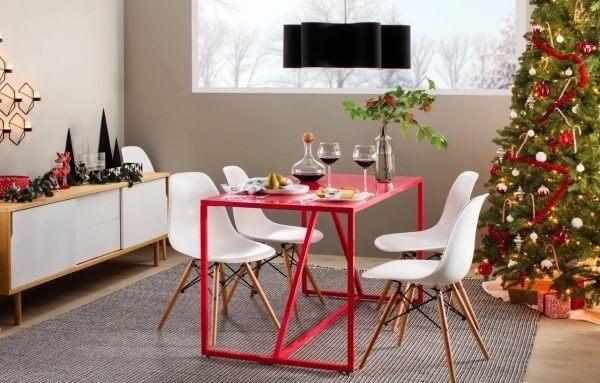 Hình ảnh cận cảnh mẫu bàn ăn màu đỏ kết hợp ghế ngồi màu trắng, cạnh đó là cây thông Noel lớn