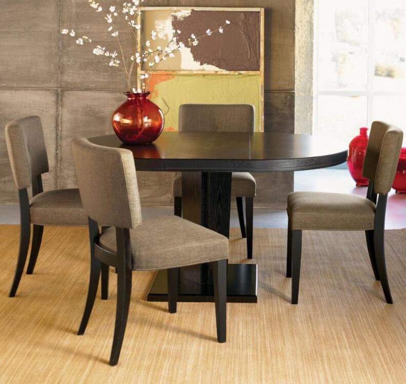 Hình ảnh cận cảnh bàn ăn hình oval màu đen, trên bàn đặt bình hoa đỏ đẹp mắt