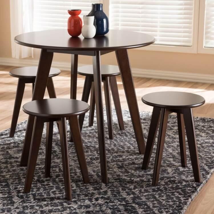 Cận cảnh mẫu bàn ăn bằng gỗ hình tròn đặt trên thảm họa tiết đen trắng, trên bàn đặt 3 bình mùa xanh dương, đỏ, trắng