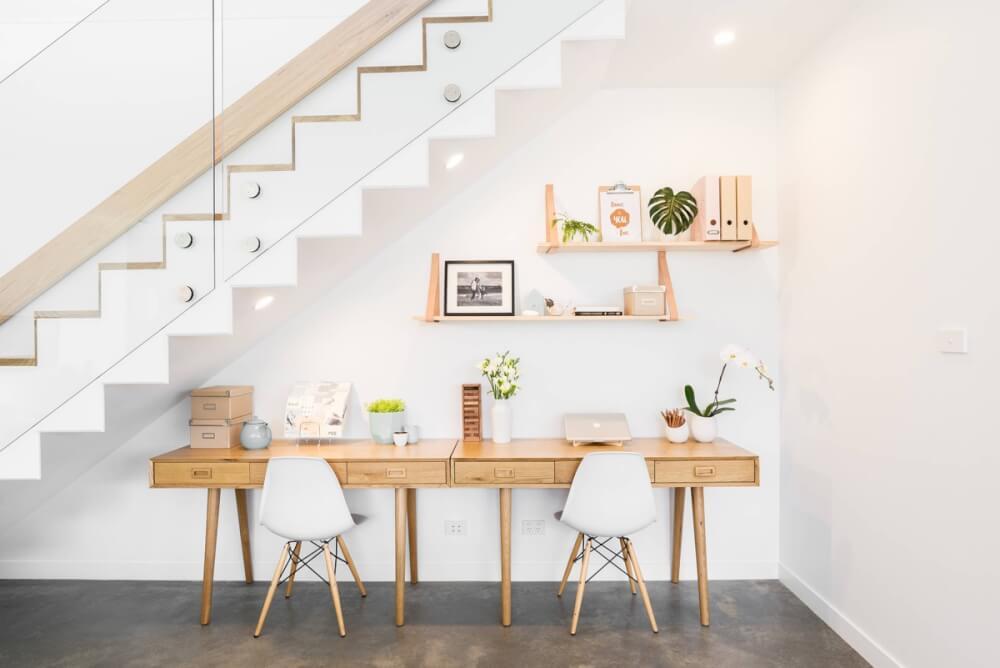 Khoảng trống gầm cầu thang được thiết kế thành góc làm việc tuyệt đẹp với bàn gỗ ngăn kéo, ghế tựa màu trắng, trang trí cây xanh sinh động.