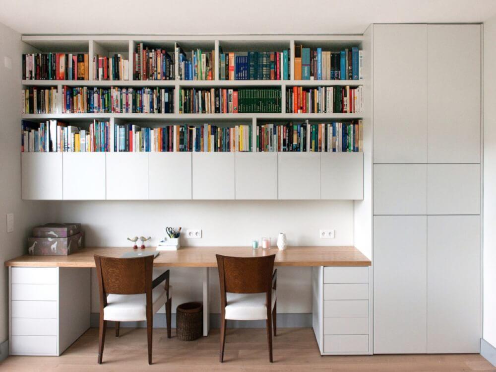 Hình ảnh phòng làm việc màu trắng chủ đạo, hai ghế gỗ, giá sách với nhiều sách báo nhiều màu
