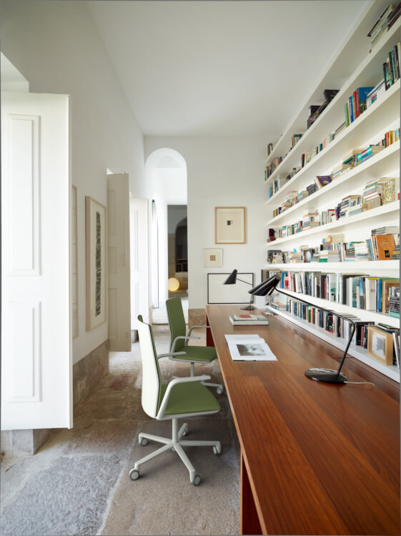 Bàn làm việc và giá sách tạo thành một khối thống nhất với sự tương phản màu sắc khá hút mắt. Cặp đôi ghế ngồi màu xanh lá có thể cất gọn vào gầm bàn.