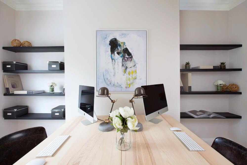 Hình ảnh góc làm việc với bàn màu trắng, ghế bọc da đối diện, kệ gỗ gắn tường màu đen, tranh và lọ hoa trang trí