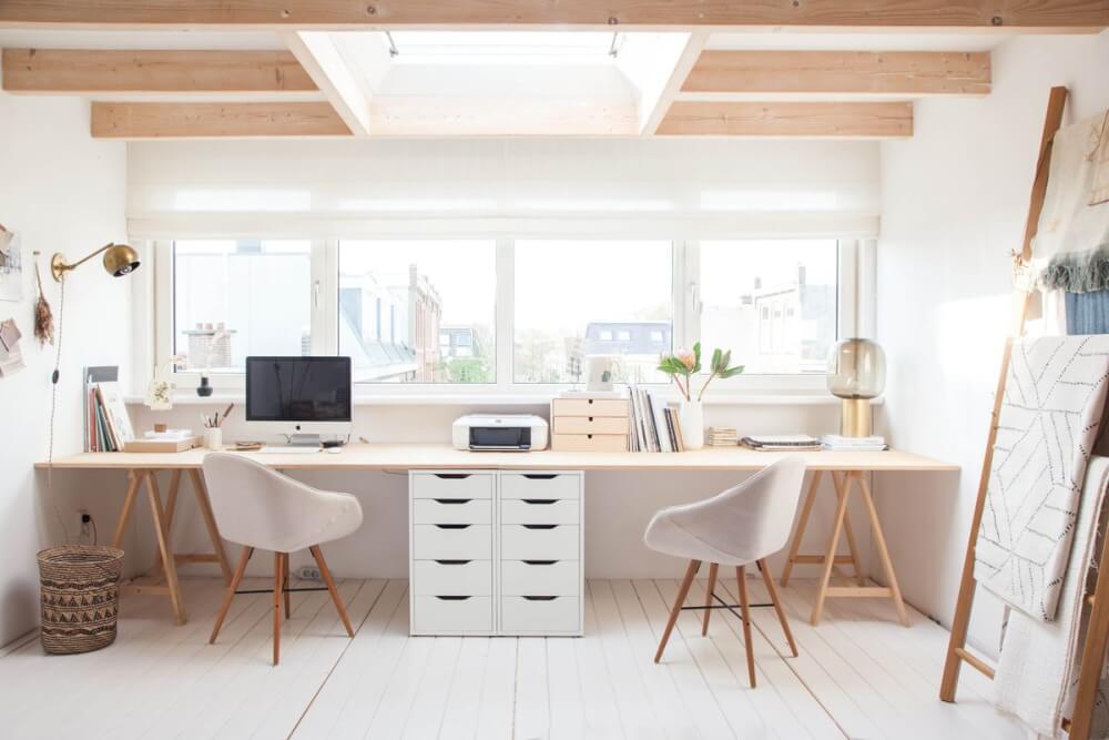 Hình ảnh góc làm việc tại nhà với bàn gỗ gắn tường, tủ ngăn kéo ở giữa, đặt cạnh cửa sổ kính