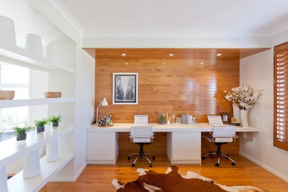 Hình ảnh văn phòng tại gia với sàn lát gỗ màu sáng, kệ lớn màu trắng đặt cây và đồ trang trí