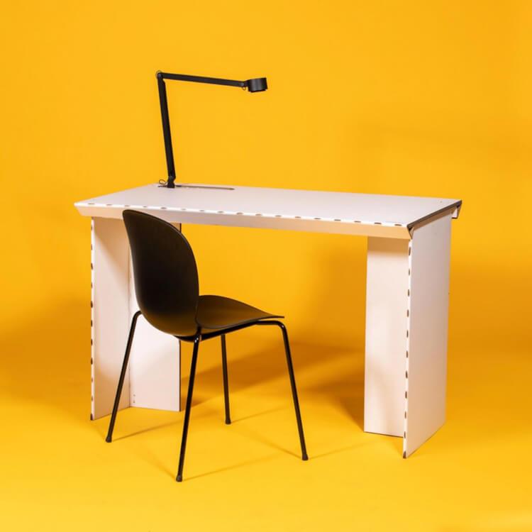 Hình ảnh mẫu bàn làm việc làm từ bìa carton màu trắng, trên đặt đèn bàn màu đen, kết hợp ghế ngồi có tựa lưng màu đen