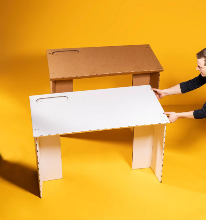 Hình ảnh một người đàn ông đang cầm vào bàn làm việc tại nhà màu trắng, cạnh đó là bàn nâu gỗ