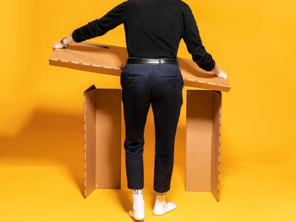 Hình ảnh một người đàn ông mặc quần áo màu đen đang lắp ráp bàn làm việc từ bìa carton cứng
