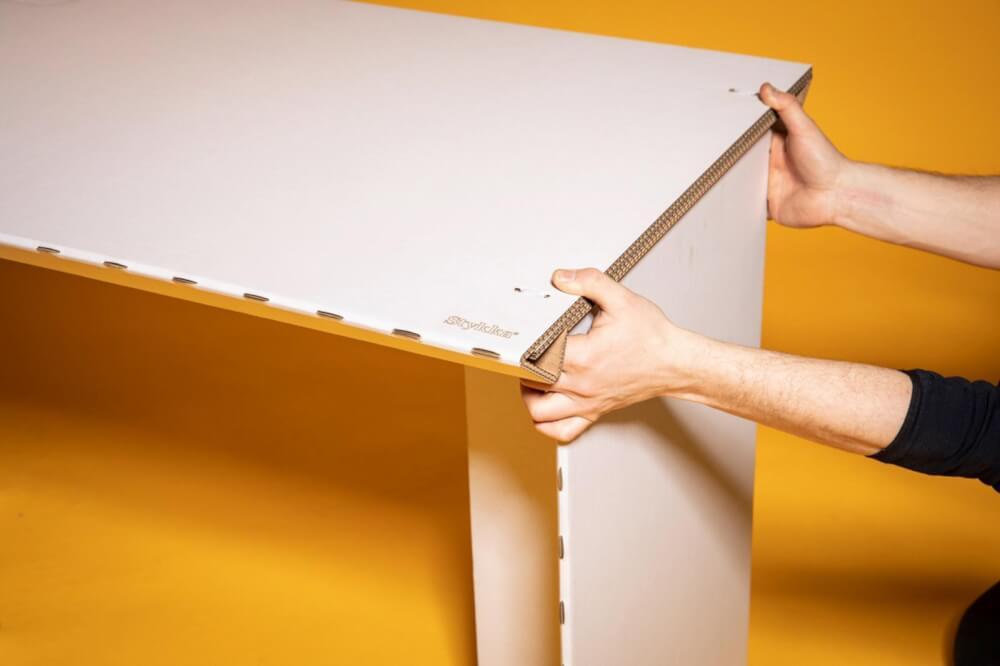 Hình ảnh đôi bàn tay một người mặc áo đen đăng lắp ráp bàn làm việc tại nhà