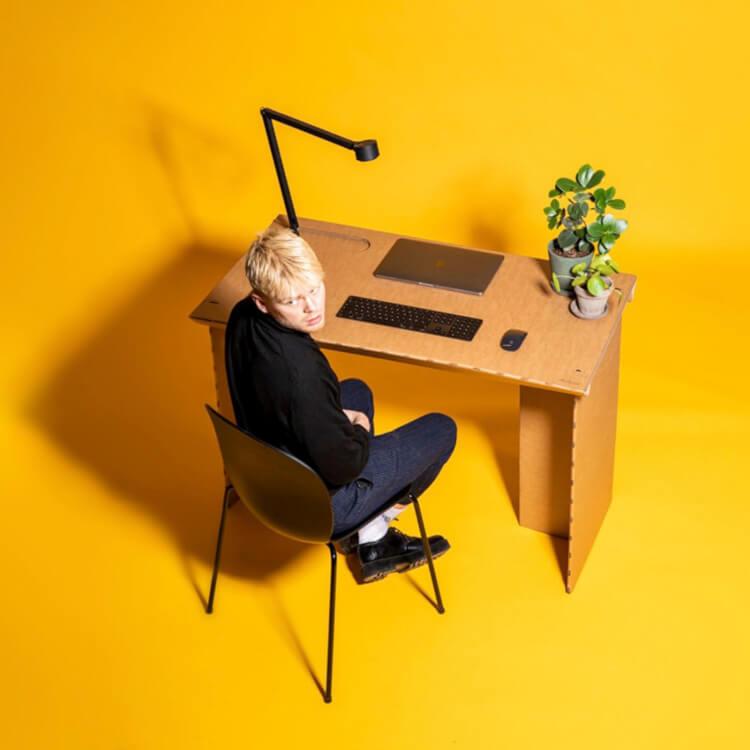 Hình ảnh một người đàn ông ngồi ở bàn làm việc từ bìa carton