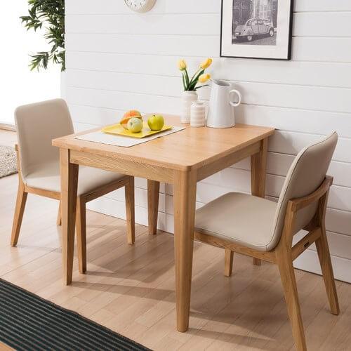 Hình ảnh cận cảnh mẫu bàn ăn hình vuông đặt sát vào tường nhà, hai ghế ngồi bọc nệm, trên bàn đặt lọ hoa trang trí