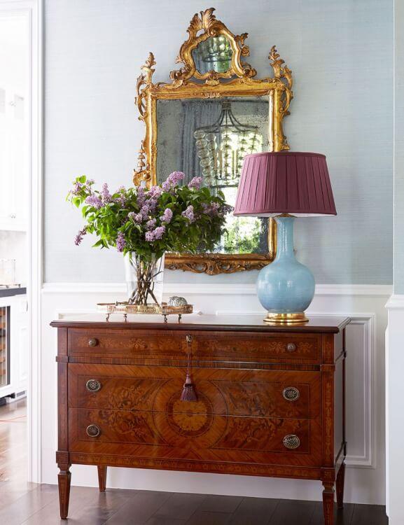 Hành lang được trang trí vô cùng ấn tượng với tường màu xanh da trời nhạt, khung gương mạ vàng kết hợp hài hòa với tủ gỗ ngăn kéo, đèn chụp màu tím và những bông hoa tử đinh hương mềm mại.