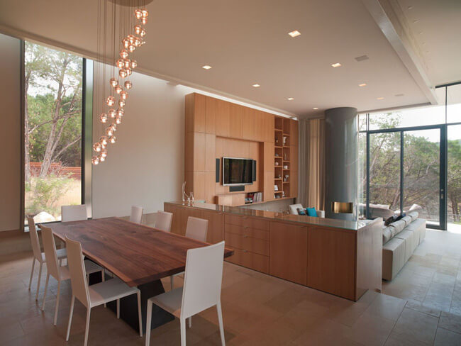 Hình cảnh cận cảnh phòng ăn với bàn ghế gỗ và đèn thả sợi đốt màu vàng ấm áp