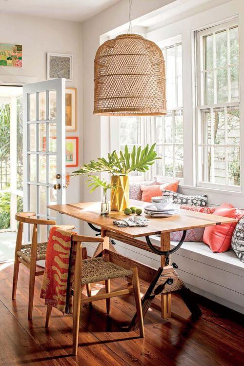 Hình ảnh góc bàn ăn ạnh cửa sổ với gối tựa màu sắc, đèn thả bằng mây tre đan mộc mạc