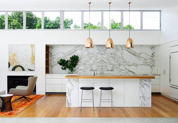 Hình ảnh cận cảnh đảo bếp bằng đá cẩm thạch trắng, đèn thả trang trí