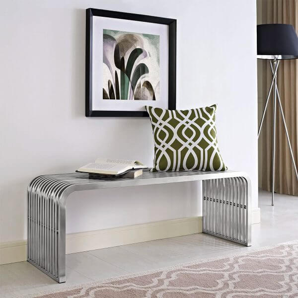 Hình ảnh mẫu ghế ngồi bằng thép không gỉ, trên đặt gối tựa màu xanh lá, tranh treo tường trừu tượng