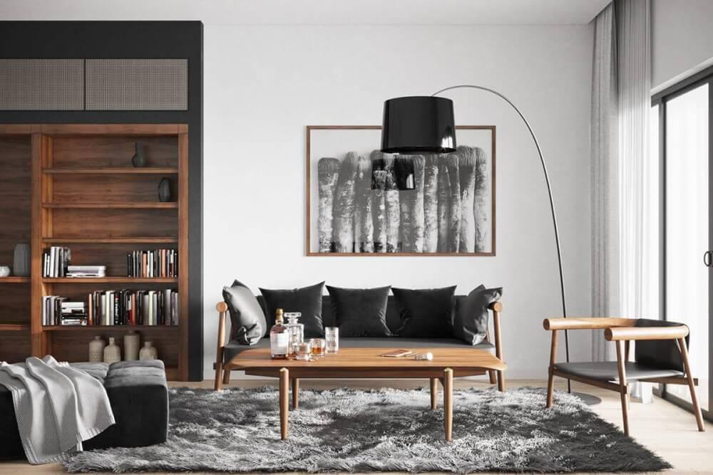 Hình ảnh phòng khách ấn tượng với tường và trần màu trắng, sàn gỗ ấm áp, sofa đen, bàn trà gỗ đặt trên thảm trải lông mềm mại