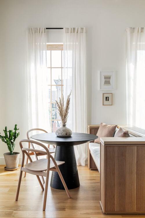 Hình ảnh phòng ăn nhỏ với bàn tròn màu đen, ghế gỗ kết hợp băng ghế dài, bình cây xương rồng tạo điểm nhấn