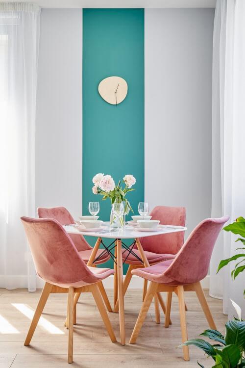 Hình ảnh phòng ăn nhỏ với ghế hồng pastel bao quanh bàn tròn, cạnh đó là bức tường xanh dương tạo điểm nhấn