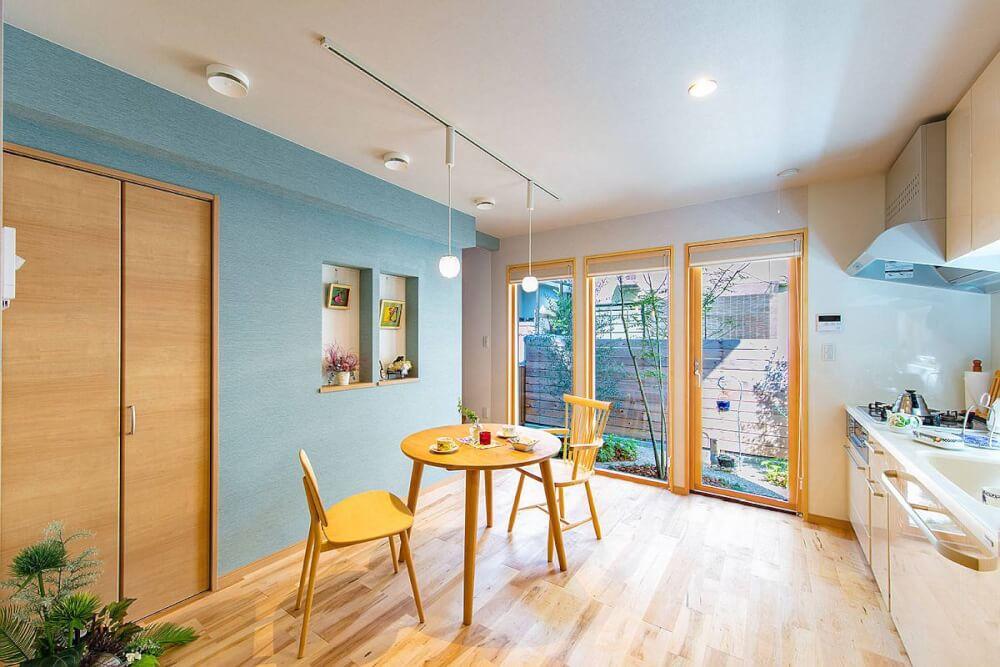 Hìnih ảnh cận cảnh bộ bàn ăn bằng gỗ màu sáng dành cho hai người đặt trong phòng có cửa kính lớn