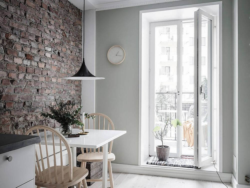 Hình ảnh bộ bàn ăn nhỏ màu trắng dành cho hai người đặt cạnh bức tường gạch nung thô mộc