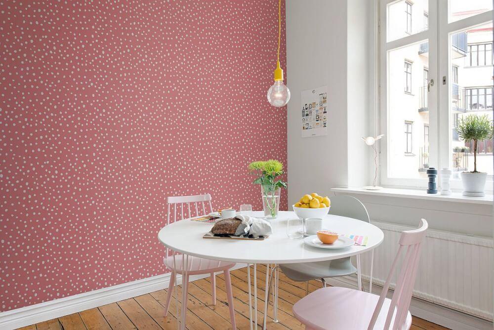 Hình cảnh cận cảnh bộ bàn ăn hình tròn đặt cạnh bức tường màu hồng chấm trắng, đèn thả sợi đốt tạo điểm nhấn