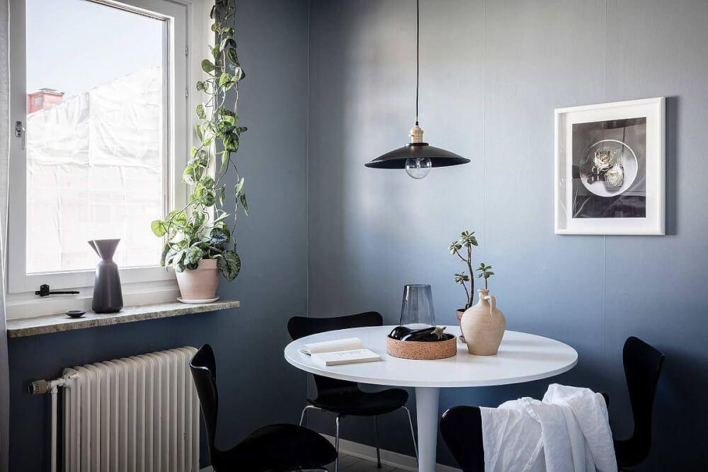 Hình ảnh phòng ăn với tường sơn màu xanh nhạt, bàn tròn nhỏ màu trắng kết hợp ghế đen đặt cạnh cửa sổ kính