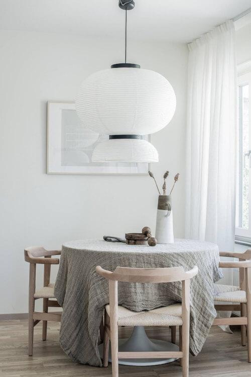 Hình ảnh phòng ăn nhỏ màu trắng với bàn gỗ tròn phủ khăn trải xám, đèn thả khổ lớn tạo điểm nhấn ấn tượng