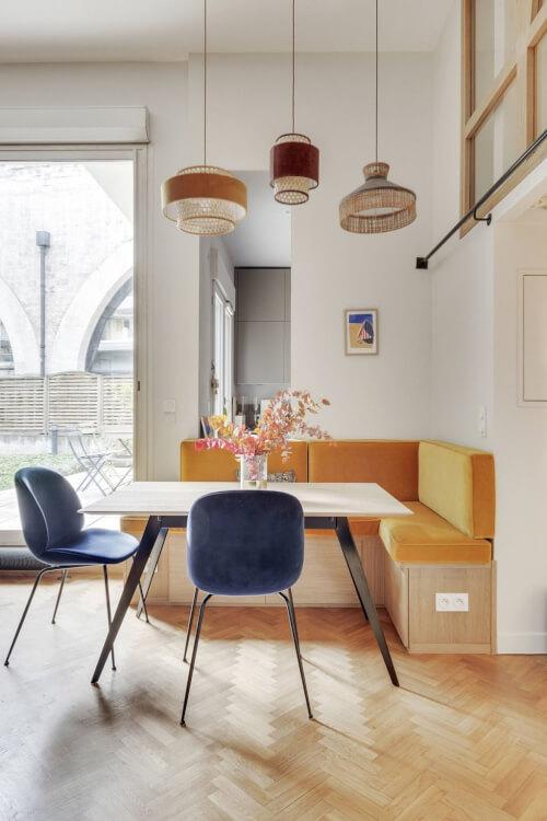 Hình ảnh phòng ăn nhỏ cạnh cửa kính với ghế tựa, bàn tròn, băng ghế sát tường