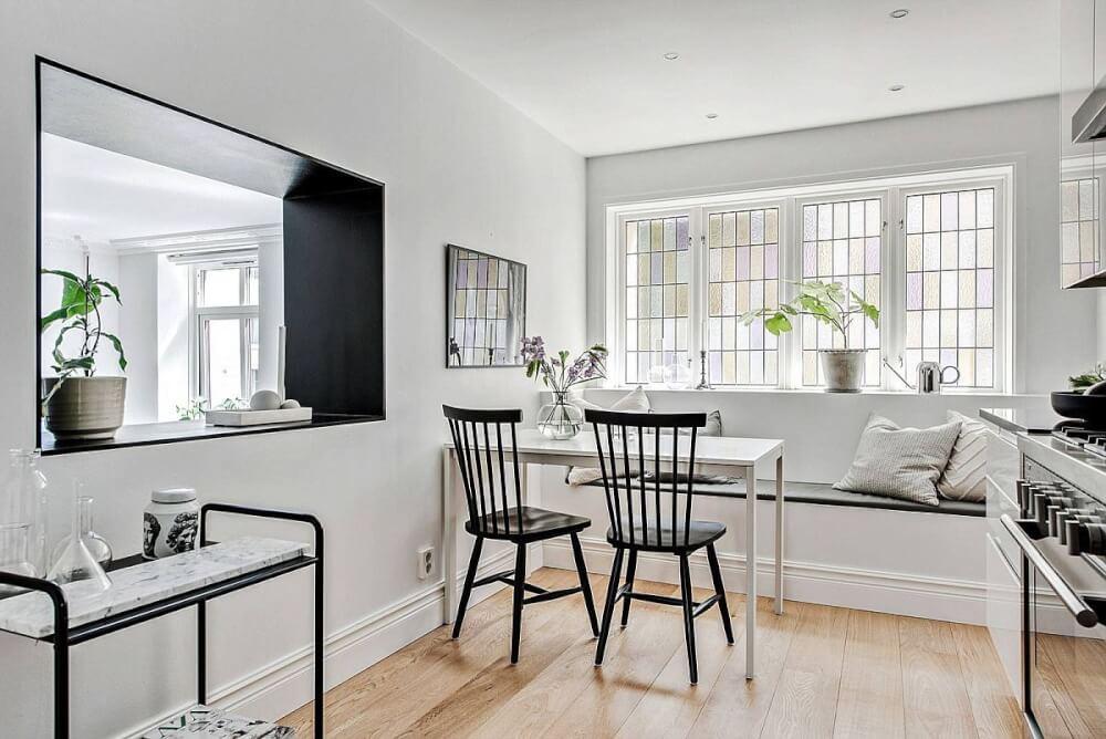Hình ảnh toàn cảnh phòng ăn nhỏ màu trắng nổi bật với cặp ghế màu đen, khung tường đen, kệ đen