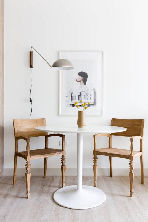Hình ảnh cận cảnh bàn ăn tròn nhỏ màu trắng kết hợp hai ghế gỗ