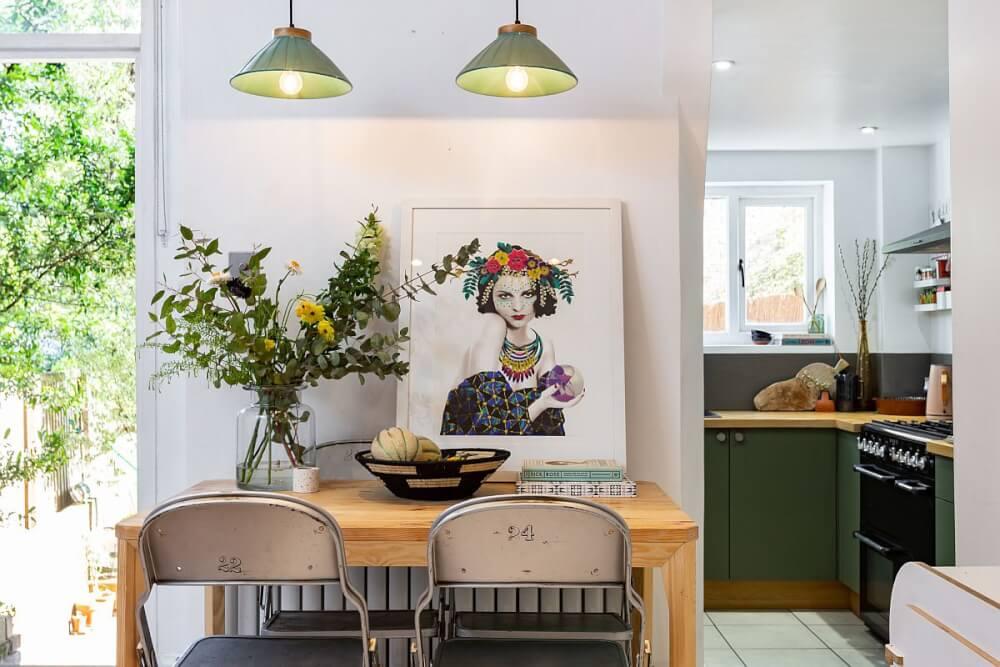 Hình ảnh phòng ăn với chụp đèn màu xanh lá, bình cây thủy tinh trong suốt, tranh nghệ thuật treo tường