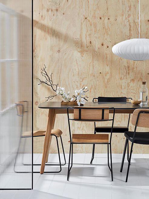 Hình ảnh một góc phòng ăn với mảng tường ốp gỗ màu sáng ấm áp, bàn ghế kiểu dáng thanh mảnh, vách kính trong suốt