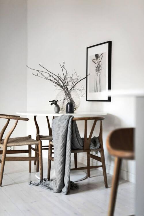 Hình ảnh cận cảnh góc ăn uống phong cách Japandi với bàn tròn nhỏ xinh, phía trên đặt bình cây trang trí tinh tế, xung quanh đặt ghế tựa gỗ mộc mạc.