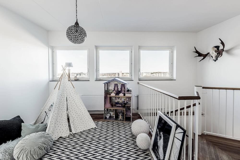 Hình ảnh phòng chơi cho trẻ ở khu vực cầu thang với lều, thảm trải,đèn thả tông màu đen - trắng kết hợp
