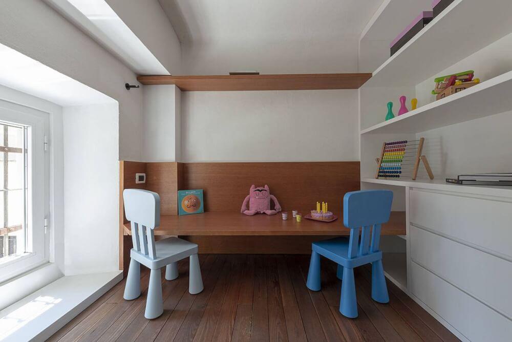 Hình ảnh góc vui chơi cho trẻ trong phòng ngủ với bàn gỗ thấp, ghế tựa sắc màu, giá mở gắn tường