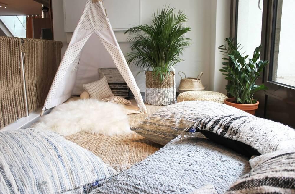 Hình ảnh góc vui chơi cho trẻ với lều vải họa tiết đen - trắng, thảm lông, đệm sàn và nhiều gối tựa, cây xanh tạo điểm nhấn