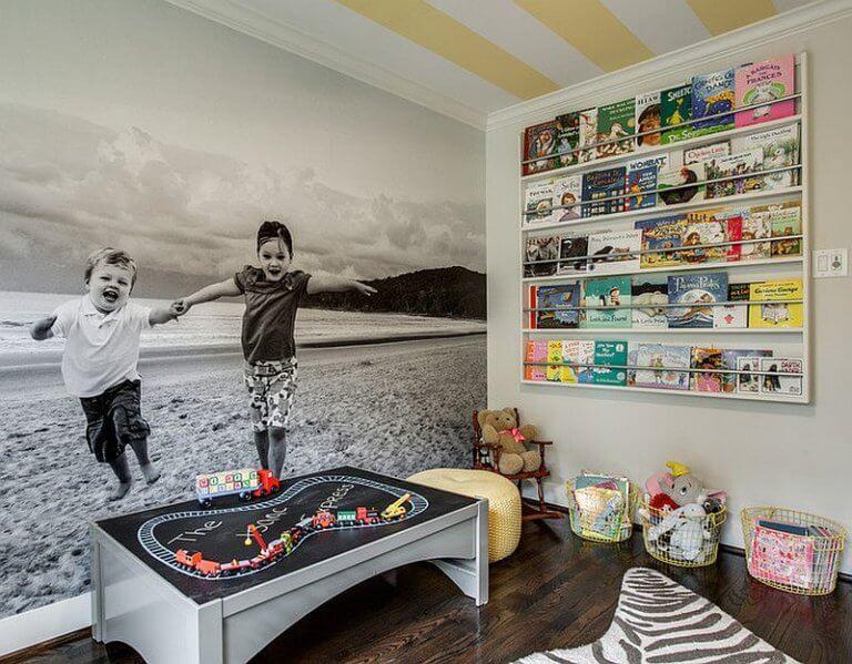 Hình ảnh phòng chơi của bé với tranh tường hai chị em nô đùa, giá sách treo tường, giỏ đựng đồ chơi