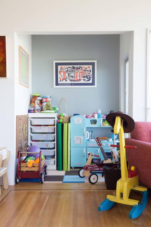 Hình ảnh sân chơi trong phòng ngủ của bé với thảm trải màu sắc, tủ kệ nhỏ xinh