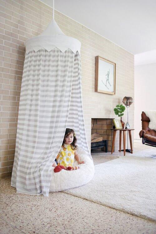 Hình ảnh bé gái ngồi trong màn treo buông rũ từ trần xuống, bên trong là gối đệm êm ái màu trắng