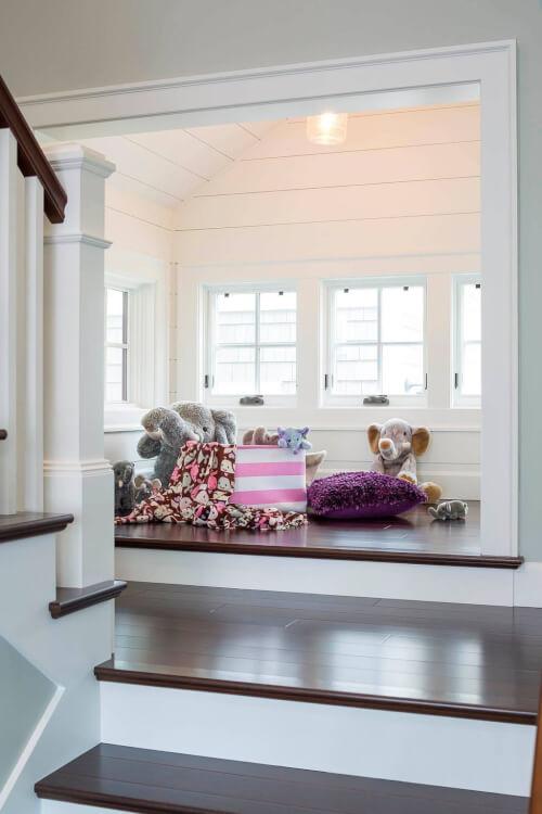 Hình ảnh cận cảnh phòng chơi cạnh cửa sổ kính với đệm sàn và những con thú nhồi bông mềm mại