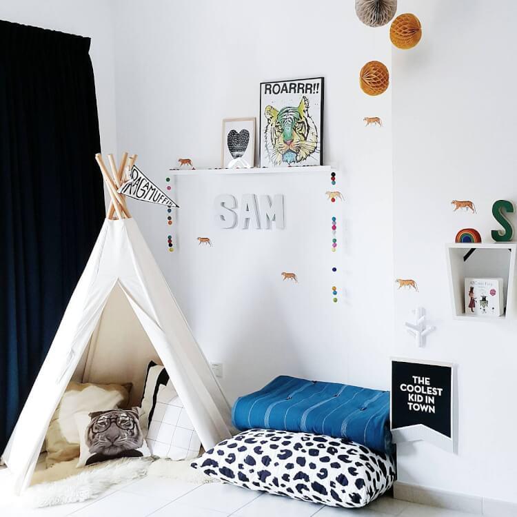 Hình ảnh cận cảnh phòng chơi cho bé trai với lều trắng, đếm àn, chăn gối êm ái