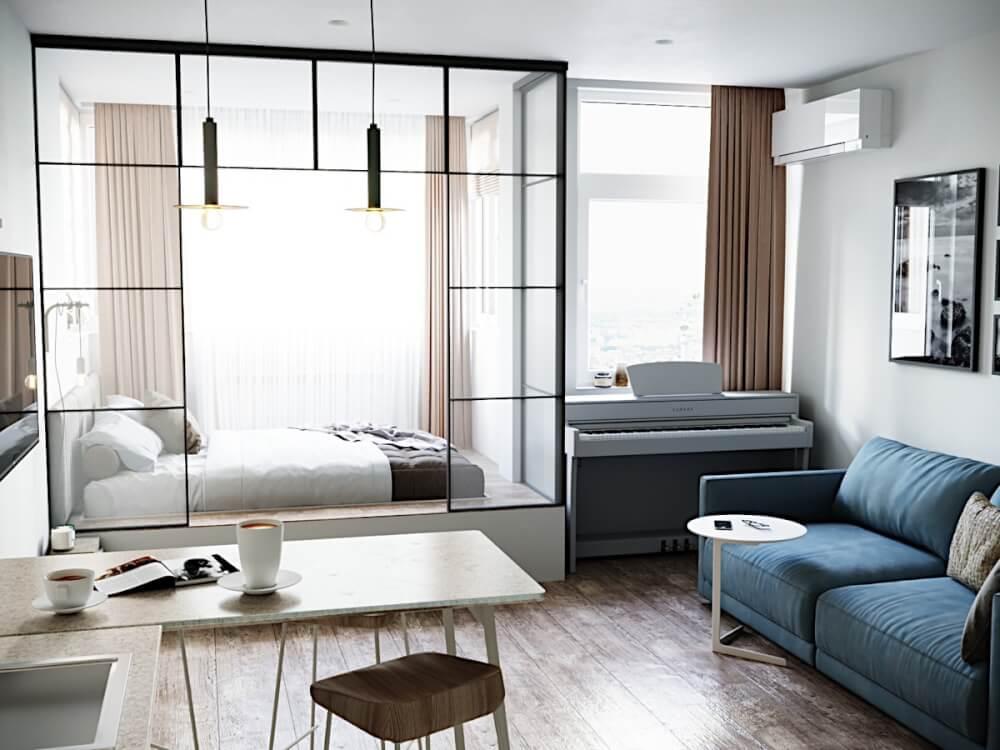 Hình ảnh bên trong căn hô studio với sofa xanh dương, cạnh đó là bàn ăn, góc đặt đàn piano, phòng ngủ sau vách kính trong suốt