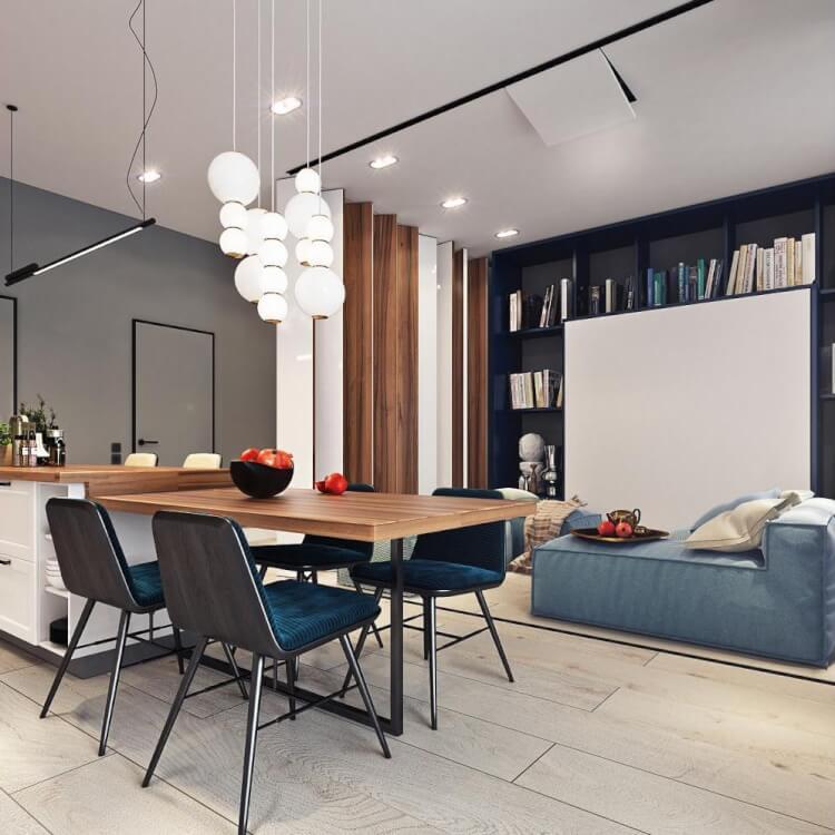 Hình ảnh cận cảnh bàn ăn gỗ, ghế ngồi lót đệm xanh, đèn thả trần độc đáo