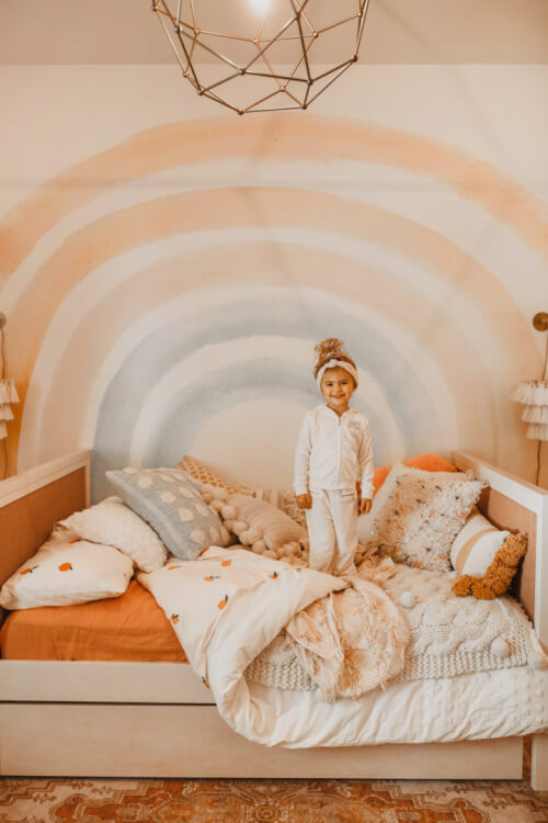 Hình ảnh một bé gái đang đứng chơi trên giường nệm êm ái