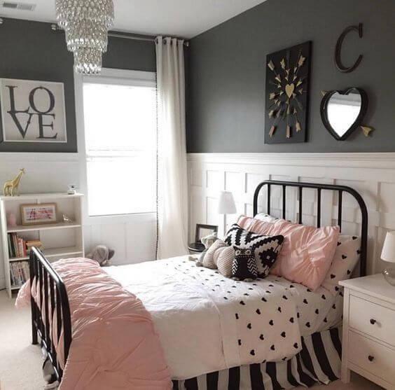 Hình ảnh phòng ngủ bé gái với giường sắt chăn gối màu hồng, ga họa tiết trái tim màu đen