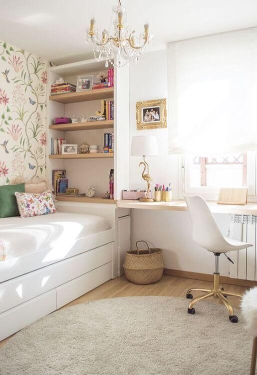 Phòng ngủ nhỏ với giường hộp ngăn kéo, giấy dán tường họa văn, đèn chùm, bàn học cạnh cửa sổ kính, giá sách đầu giường