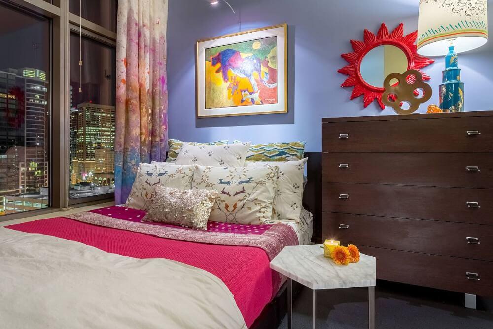 Hình ảnh phòng ngủ màu sắc tươi sáng với tường xanh da trời, ga gối màu hồng - trắng, rèm cửa màu tím nhạt