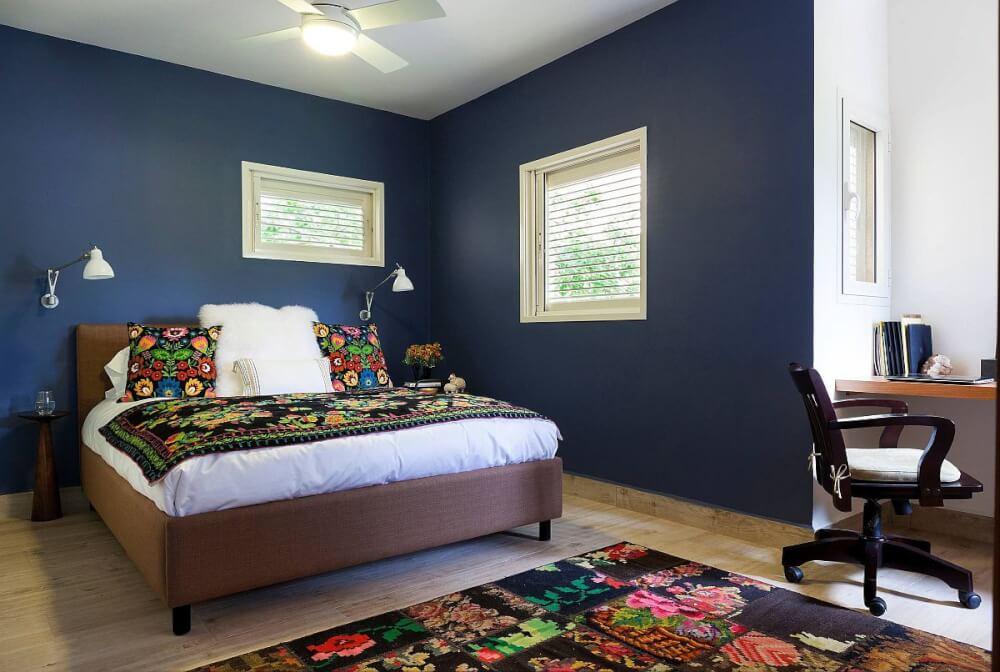 Hình ảnh phòng ngủ với tường màu xanh đậm, cửa sổ kính, ga gối họa tiế hoa màu đỏ